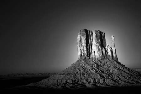 Dramatic light of dawn striking a rock formation in the Navajo nation land of Monument Valley in black and white photo