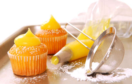 Decorating cupcakes with lemon curd and powdered sugar photo