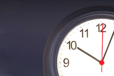 Closeup of a clock agains a blue wall showing time ticking away