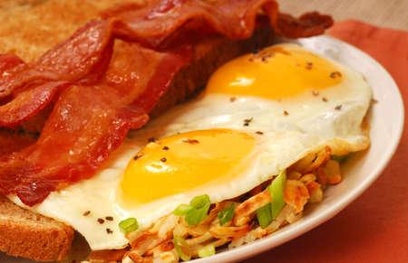 papas doradas: Gran desayuno de huevos, tocino, tostadas y hash browns Foto de archivo
