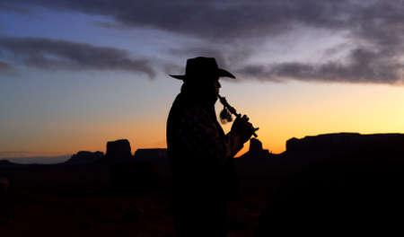 dwarsfluit: Native American Navajo Indian een traditionele fluit spelen bij zonsopgang over Monument Valley Stockfoto