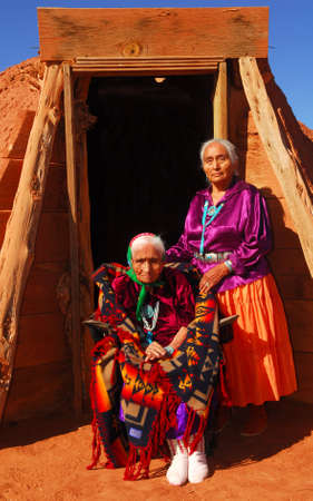 Elderly 99 year old Navajo Native American woman and her daughter standing in front of a traditional Hogan photo