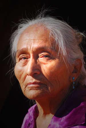 Oudere Navajo vrouw met licht schijnt op haar gezicht