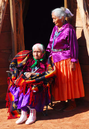 the dwelling: 99 year old Navajo woman with her daughter in front of a traditional Hogan dwelling Stock Photo