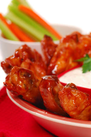 Hot and spicy chicken wings with blue cheese dipping sauce and carrot and celery sticks
