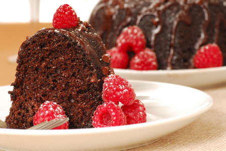 Fresh chocolate fudge cake with raspberries and powdered sugar in a romantic holiday setting photo