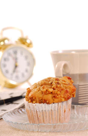 Freshly baked banana nut muffin with coffee, alarm clock and crossword puzzle photo