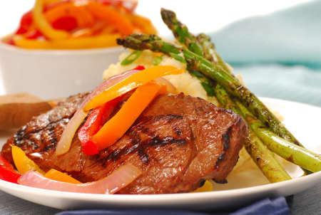 Grilled rib-eye steak with mashed potatoes and asparagus Stock Photo