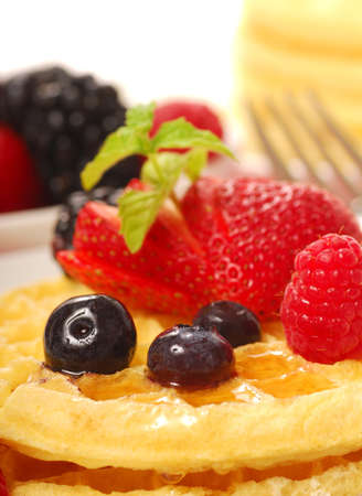 Freshly made waffles with a variety of fruit and maple syrup photo