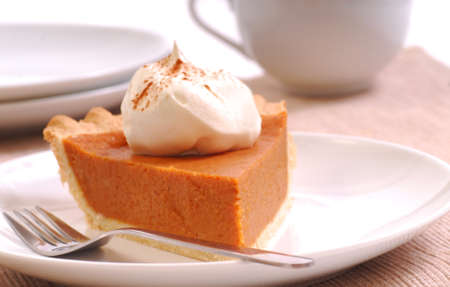 pumpkin pie: Slice of freshly made pumpkin pie with whipped cream and cinnamon