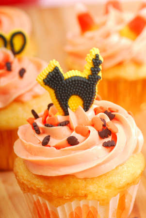 Delicious Halloween cupcakes being frosted and decorated photo
