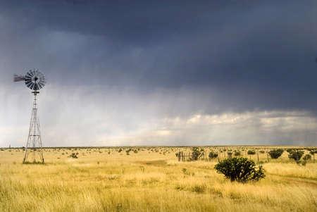 Molino de viento en un campo de Texas a lo largo de la ruta 66 con una tormenta acercarse a