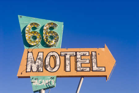 Old rusted Route 66 motel sign in front of an abandoned motel