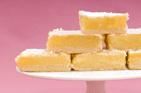Heerlijke vers gebakken citroen vierkantjes op een witte cake stand