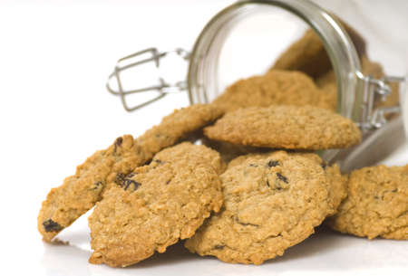 Delicious freshly baked oatmeal raisin cookies spilling out of a glass container