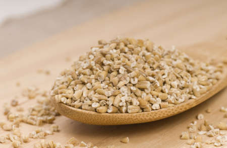 Fresh steel cut oats on a wooden spoon photo