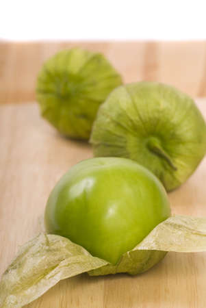 Three fresh tomatillos on a cutting board photo
