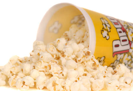 corn kernel: Container of delicious movie popcorn with popcorn spilling out