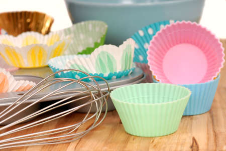 Variety of cupcake liners in different colors with a muffin pan and wire wisk