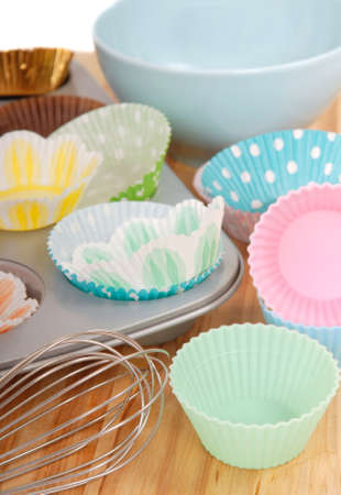 food supply: Variety of cupcake liners in different colors with a muffin pan and wire whisk