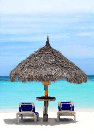 Thatched hut on a stretch of beach in Aruba overlooking the Caribbean Sea photo