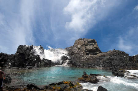 Waves crashing over the rocks surrounding the Natural Pool in Aruba Stock Photo