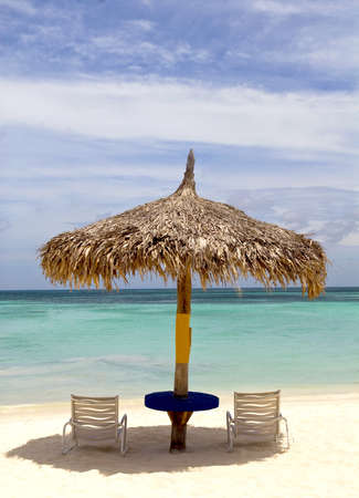 Thatched hut on a stretch of beach in Aruba overlooking the Caribbean Sea