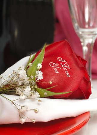 Romantische Red Rose die zegt Ik hou van jou geschreven op het op een bord met een glas champagne Stockfoto