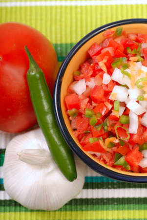 tex: Bowl of spicy salsa with tomato, garlic and serano pepper