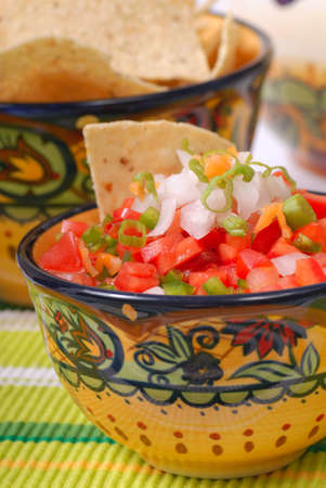 tex: Bowl of spicy salsa with tortilla chips in the background Stock Photo
