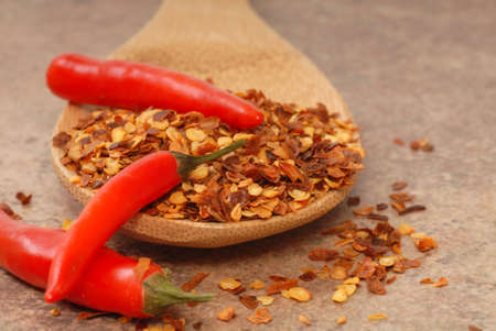 pepper flakes: Hot red chili peppers and red pepper flakes on a wooden spoon Stock Photo
