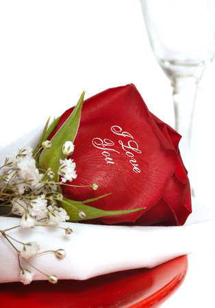 Romantic Red Rose that says I Love You written on it on a dinner plate with a champagne glass