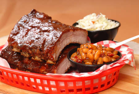 Delicious BBQ ribs with beans, cole slaw and a tangy BBQ sauce Stock Photo