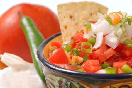 Fresh spicy salsa with tortilla chips along with the ingredients for the salsa