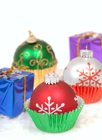 Festive Christmas ornaments placed in cupcake liners with snow and wrapped gift boxes photo