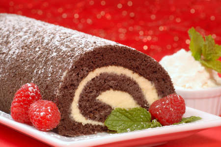 christmas cake: Delicious Christmas Buche de Noel cake with raspberries, whipped cream and powdered sugar Stock Photo