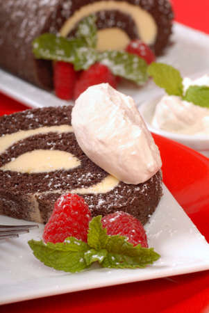 Delicious Christmas Buche de Noel cake with raspberries, whipped cream and powdered sugar photo