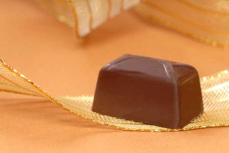 Delicious dark chocolate bonbon resting on a gold ribbon Stock Photo