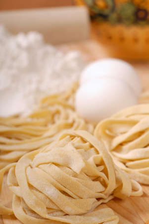 Delicious freshly made fettuccine pasta with eggs and rolling pin