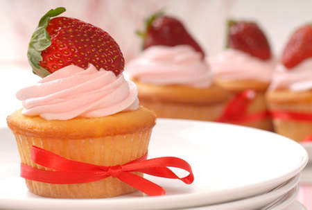 Delicious vanilla cupcake with strawberry frosting and a fresh strawberry photo