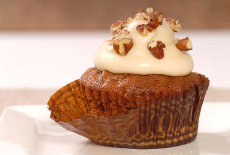 mouthwatering: Delicious carrot cake cupcake with cream cheese frosting and chopped pecan nuts