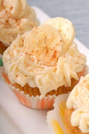 Delicious vanilla cupcake with cream cheese frosting, bananas and cinnamon  photo