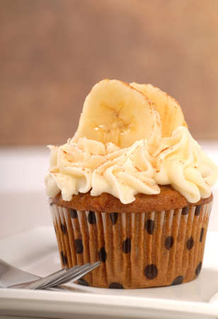Delicious carrot cake cupcake with cream cheese frosting, bananas and cinnamon  photo