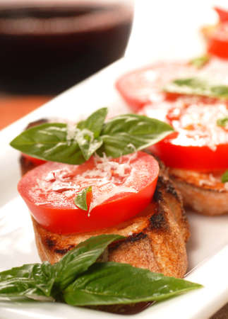 hardy: Delicious Bruschetta with tomato and basil on a white place with a glass of wine in the background
