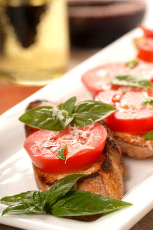 Delicious Bruschetta with tomato and basil on a white place with a glass of wine in the background along with an oil and vinegar vinaigrette  photo