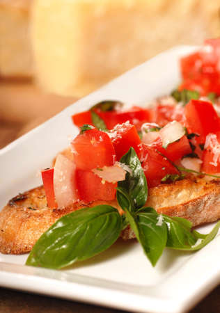 Delicious Bruschetta with tomato, mozzarella and basil with Parmesan cheese in the background photo