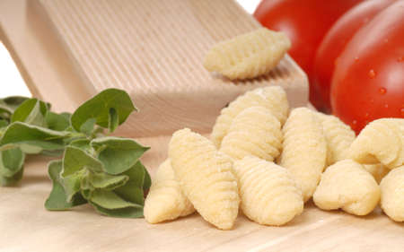 Delicious hand made Gnocchi using a Gnocchi board with tomatoes and herbs photo