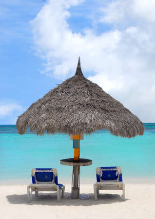 thatched: Thatched roof hut on a beautiful white sand beach in Aruba overlooking the Caribbean Sea