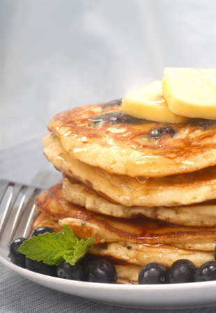 Delicious homemade blueberry pancakes with pure maple syrup dripping down them photo
