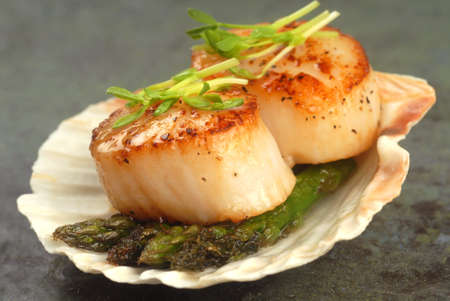 seared: Delicious pan seared sea scallop with asparagus and pea shoots served on a scallop shell Stock Photo